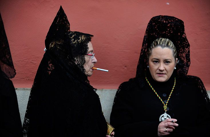 "Women in traditional mantilla dresses smoke outside church before taking part in the Brotherhood procession of ""Los Estudiantes"" (The Students) at the start of Holy Week in Oviedo, northern Spain"