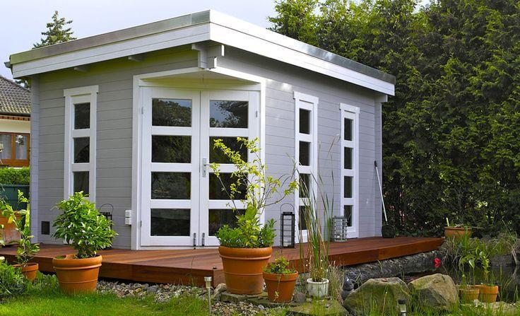 Helles Flachdach Gartenhaus umgeben von einer tollen Holzerrrasse am Gartenteich gelegen.