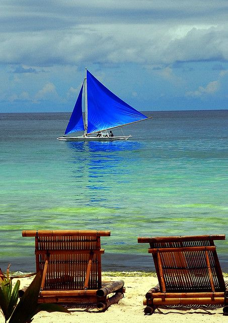 A blue sailed banca passing by a serene seaside in Bora, Philippines