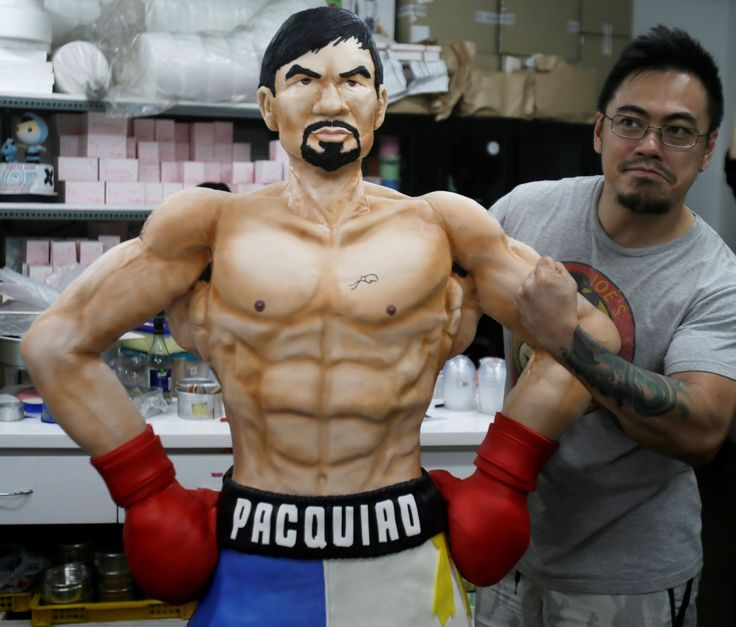 Zach Yonzon, owner of The Bunny Baker cafe, poses with the life-sized cake of Filipino boxer Manny P... - AP Photo/Bullit Marquez