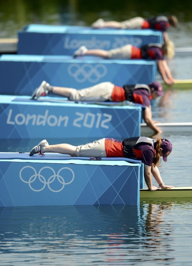 Race officials hold the boats in place before the lightweight men's rowing four heat at the Eton Dorney during the London 2012 Olympic Games July 28, 2012.