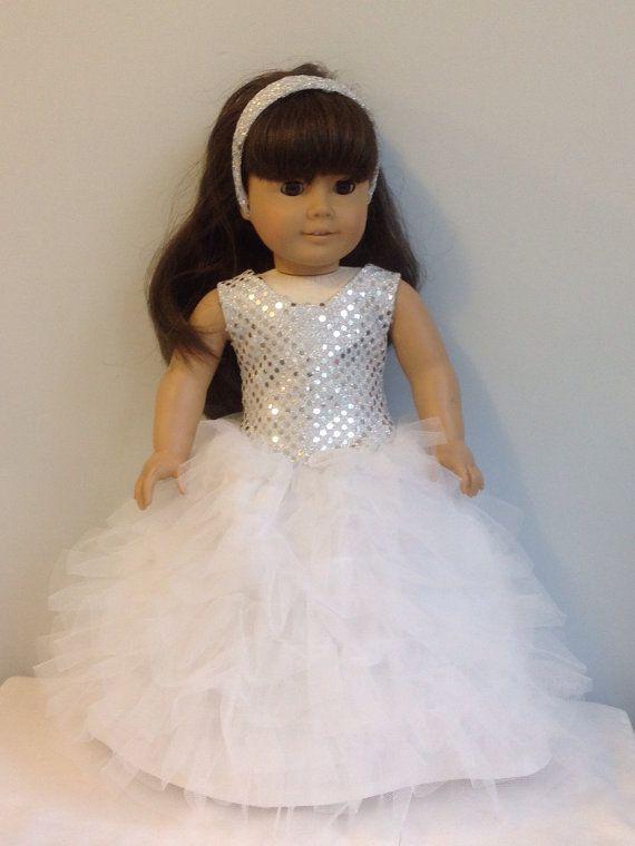 Convient comme vêtements de poupée American Girl, 18 pouces, vêtements de poupée, ou des vêtements de poupée AG  Il s'agit d'une robe de taille de goutte avec une jupe en tulle plusieurs niveaux. Il est fait d'une version modifiée d'un modèle de robe de Mackenzie Genniewren qui peuvent être trouvés à Pixiefaire.com.  Ce top est fait à partir de matériaux éclat argenté et est doublé de satin blanc. La jupe est faite de blanc satinée et est recouvert de rangées de tulle froncé.  La couleur et…