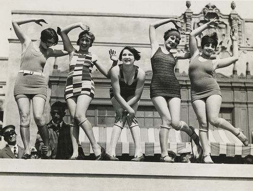 c. 1920. I think they're doing the Charleston in swimsuits...and I am wondering about that creepy man grabbing that woman's ankle :\