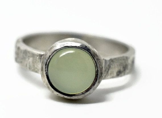 This dyed aqua chalcedony gemstone is 8mm with a round cabochon cut. Weve set it in a chunky sterling silver bezel setting. The ring band is