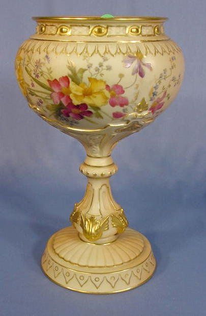 Royal Worcester Stemmed Vase: the bowl has multi floral decoration. The molded stem ends in gold colored wing and leaf designs. Marked for the year 1911