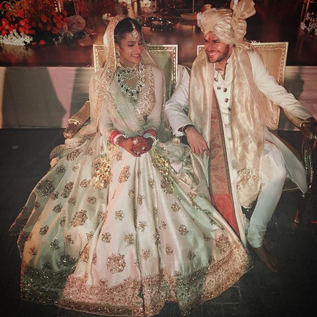 Image via @rheakapoor Bride wearing a cream Sabyasachi lehenga. Grooms adorns a Raghavendra Rathore sherwani.