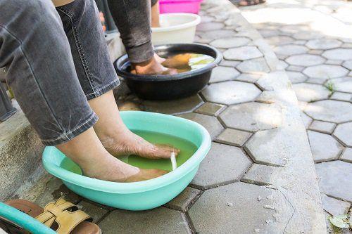 mujer poniendo los pies en remojo con agua y vinagre para quitar los hongos en las uñas