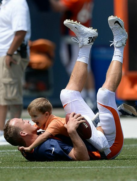 Description of . Denver Broncos quarterback Peyton Manning (18) gets tackled by his son Marshall after practice on day four of the Denver Broncos 2014 training camp July 27, 2014 at Sports Authority Field at Mile High. The kids came out to join him on the field after he signed autographs. (Photo by John Leyba/The Denver Post)