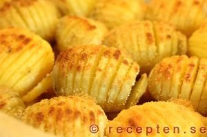 Recept på Hasselbacks-potatis.  Baked potatoes, where the potatoes are cut into thin slices halfway, and butter, breadcrumbs (and perhaps slivered almonds) have been superimposed potatoes. Hasselback potatoes was created in 1953 by Leif Elisson from Värmland, Sweden, who was a student chef at the restaurant Hasselbacken on Djurgården in Stockholm.
