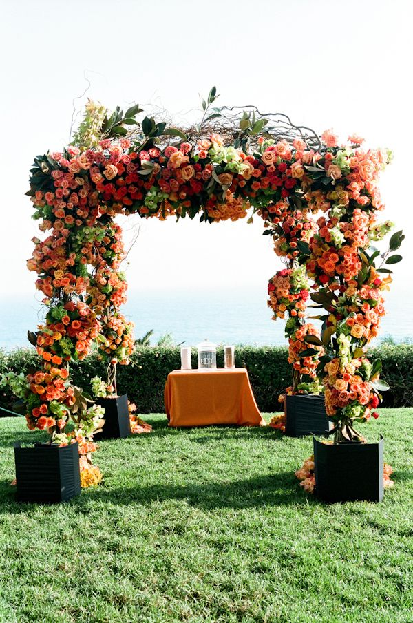 Orange and coral wedding ceremony alter decor