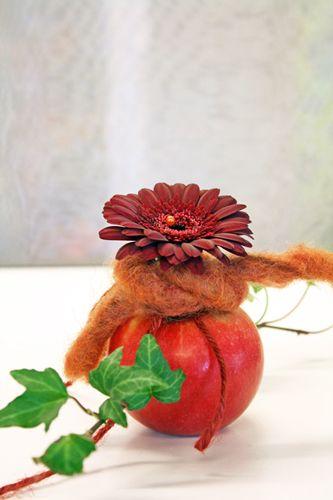 http://holmsundsblommor.blogspot.se/2010/09/varmt-om-halsen.html Bordsdekoration i äpple med germini
