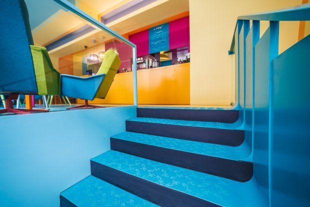Płynne przejście pasów z posadzki na ściany było inspiracją dla okładziny stopni i balustrady.