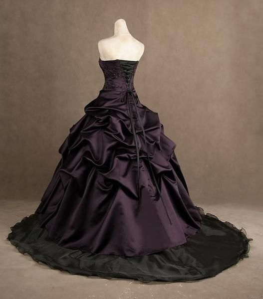 Deep plum purple over a black skirt make this an elegant choice for a Halloween or Gothic style wedding. The sleeveless corset style top has black beaded lace appliques. The full skirt (crinoline recommended for full effect) is elegant tufts of taffeta cascading over a black court skirt with court style train. Simply stunning! Dress is lovingly handmade to order and takes approximately 4-6 weeks to complete. Rush orders are available depending on the time of year. Please send a private…