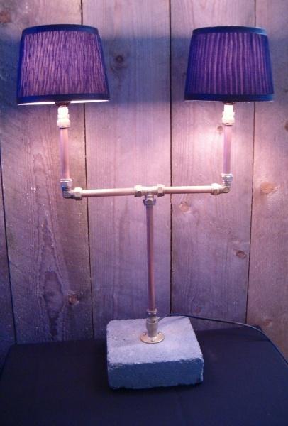 Een stoere lamp met een industriële uitstraling, gemaakt van koperen leiding en knelkoppelingen