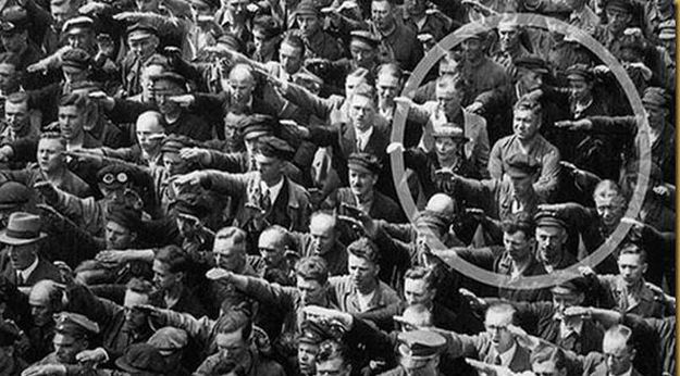 Civil disobedience. Workers at a shipyard celebrate the christening of a new ship for the navy in 1936. One man refuses to give the Hitler salute.