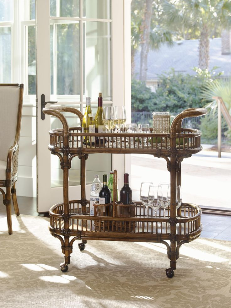 Entertain with ease with this stylish tropical bar cart. Store plenty of bottles and mixers on two cocoa shell veneers with protective coatings. For easy relocation within your home, the bar cart has metal ferrules and casters in antique brass finish and rattan wrapped handles. Make your own vacation in your home with this exotic yet elegant bar cart.