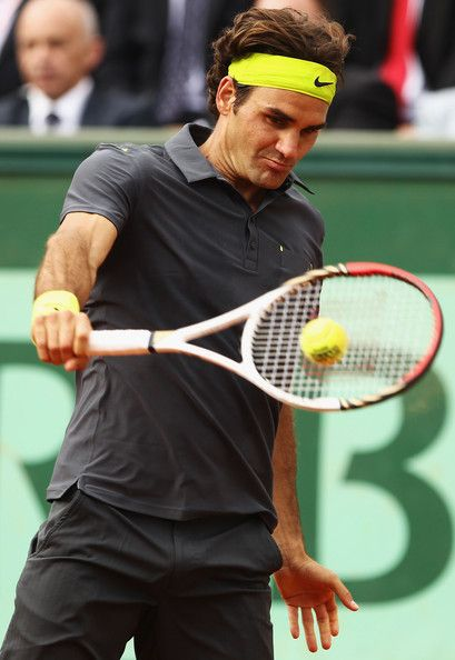 Roger Federer Photos - Roger Federer of Switzerland plays a backhand in his men's singles fourth round match against David Goffin of Belgium during day 8 of the French Open at Roland Garros on June 3, 2012 in Paris, France. - 2012 French Open - Day Eight