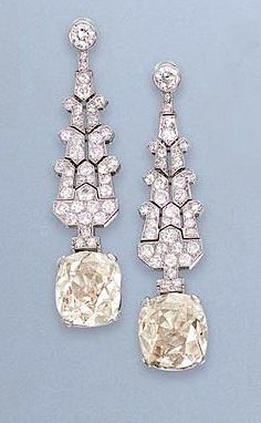 A PAIR OF ART DECO DIAMOND EAR PENDANTS, BY CARTIER Each designed as a stylised palmette tapered surmount, suspending a cushion-shaped diamond, weighing approximately 7.18 and 7.97 carats, circa 1920, 5.7 cm. long, with French assay marks for platinum and gold Signed Cartier, Paris, no. 6950