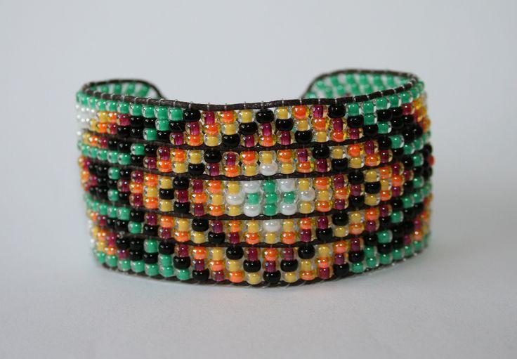 Braccialetto a telaio stile Indiano Americano a 5 binari. Perline 11/0 verdi, nere, rosse, arancione, gialle e bianche, cuoio marrone, bottone e charm color argento.