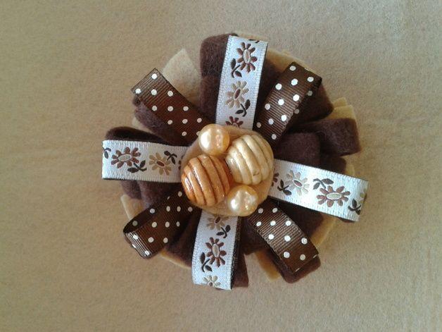 broche fieltro marron y beig, con cinta de flores tonos marrones y bolitas en el centro de madera.
