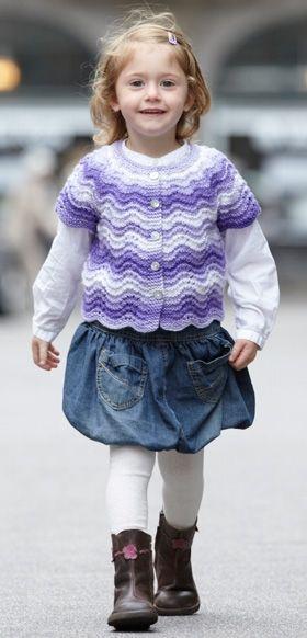 Den fine pigevest er strikket i et fint bølgemønster, hvor indtagningerne er integreret i mønstret på bærestykket