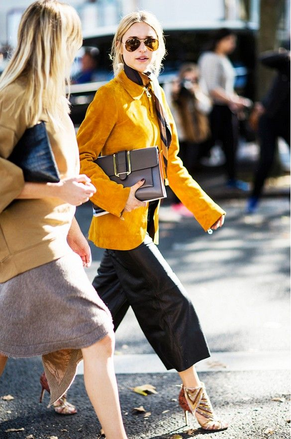 Pernille Teisbaek wears a suede jacket, neckerchief, black culottes, and strappy heels with a neutral clutch and aviator sunglasses