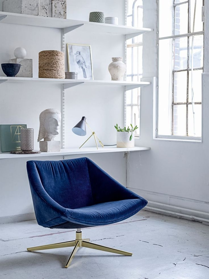 Beautiful indigo blue chair surrounded by pretty accessories and a cool lamp - together creates a stylish and modern reading corner.