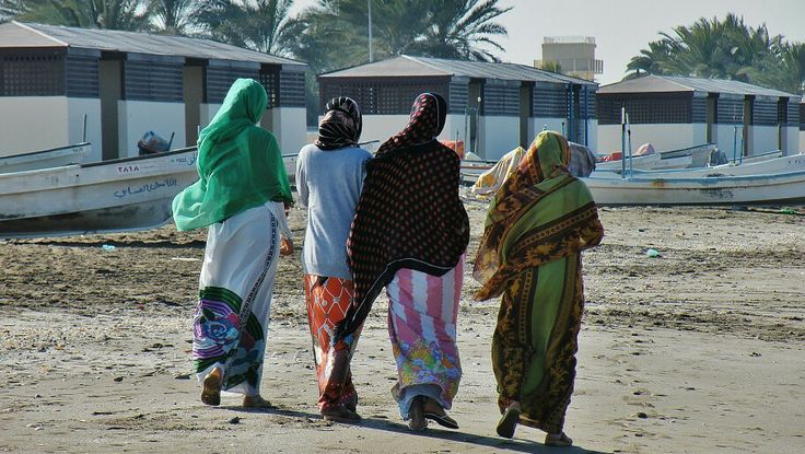 Omani women from the neighbouring fishing community in more informal attire strolling the beach, A'Mussanah, Oman, 2012.
