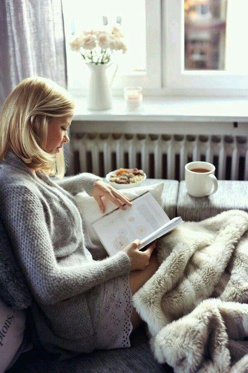 mujer sentada en un sillón al lado de la ventana leyendo y bebiendo café