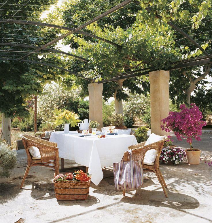 Bajo una pérgola emparrada  Comedor con sillas de fibra vegetal, que mantienen la sintonía con el entorno.  El mueble