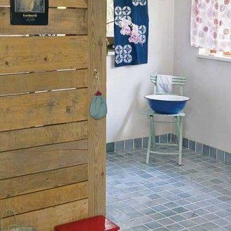 """Zasłony w łazience to znalezisko z pchlego targu. Są farbowane starą japońską techniką shibori – precyzyjne motywy powstają, gdy zawiążemy na płótnie supełki. Hiszpańskie płytki na podłodze robione na """"ręcznie robione"""". Agata specjalnie szukała nierównych, w wodnym kolorze. Emaliowana na ulubiony kolor indygo miska z IKEA, stołek pomalowała gospodyni."""