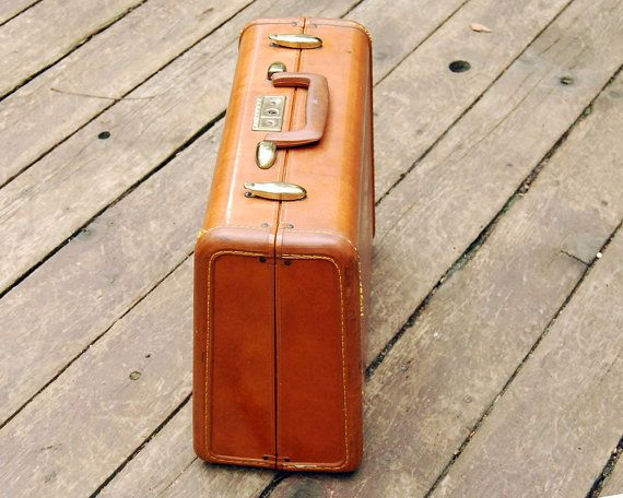 This classic vintage Samsonite suitcase is a small, relatively rare size, the vanity overnighter (male equivalent to the train case), style 4616, in caramel / orange/ brown. Its sturdy, hard-sided luggage with a faux leather outside and soft khaki lining inside. The brass finish label