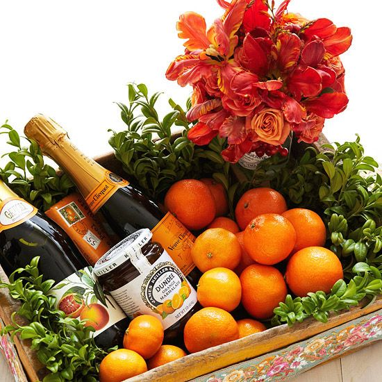 Bonus Arrangement: Festive Tray with Christmas Flowers    This arrangement, set in a wooden tray, makes a great gift. Layer boxwood stems to create the base, add a handful of small oranges or clementines, and arrange a small vase of bright roses and parrot tulips. Fill the tray with bottles of champagne or other specialty items to complete the gift.