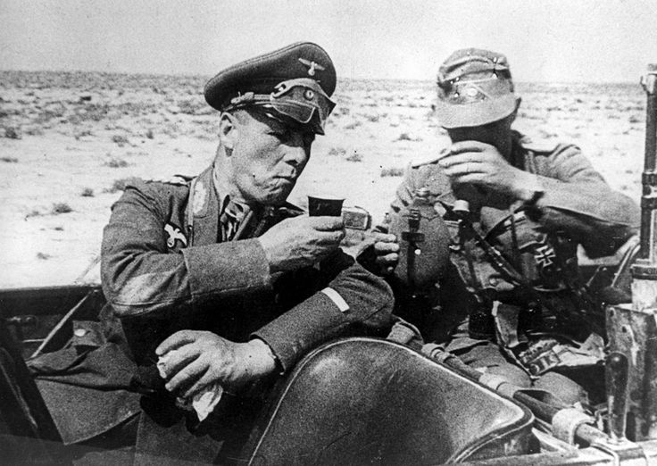 Field Marshal Gen. Erwin Rommel, commander of the German Afrika Korps, drinks out of a cup with an unidentified German officer as they are seated in a car during inspection of German troops dispatched to aid the Italian army in Libya in 1941. (AP Photo