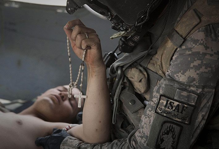 Credit: Anja Niedringhaus/AP Associated Press president Gary Pruitt described Anja as 'spirited, intrepid and fearless, with a raucous laugh that we will always remember'. Here, in this photograph taken on 11 June 2011, Lance Corporal Blas Trevino of the 1st Battalion, 5th Marines, clutches his Rosary beads as he is treated by US Army flight medic Sgt Joe Campbell on a medevac helicopter after being shot in the stomach outside Sangin, Afghanistan