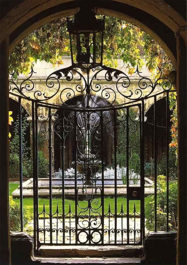 portail de jardin métallique et ornementé qui mène sur le jet d'eau