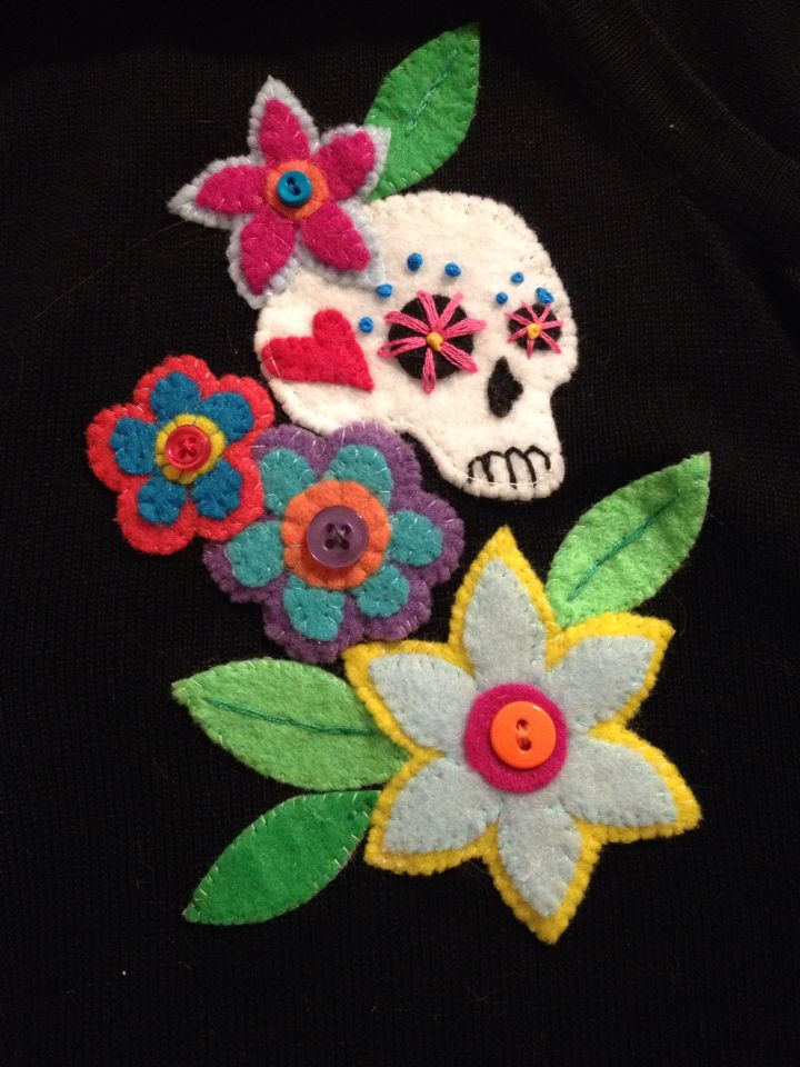 Embellished sugar skull cardigan (felt, embroidery floss, & buttons.) by Kate Allison-Mills
