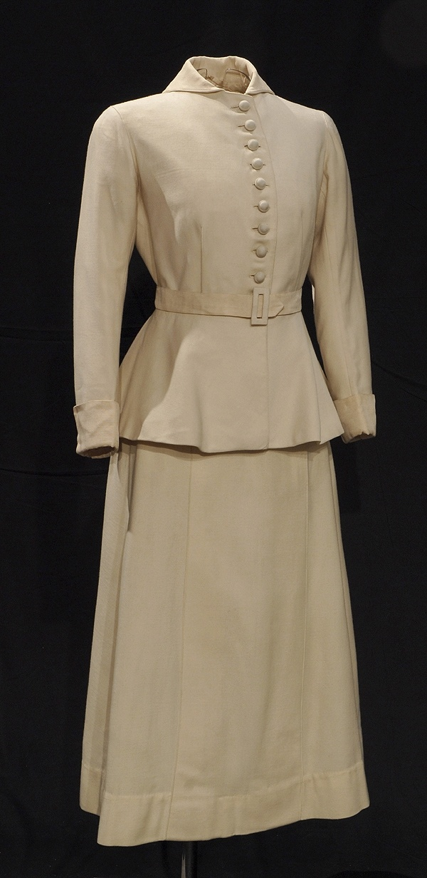 Tailored Wedding Costume, 1916.  Cream twilled wool with cream corded silk collar and cuffs. The Norfolk-style bleted jacket has hip length bias-cut basques and the skirt is the new shorter and fuller style which appeared in 1916. Wartime economy has dictated a practical choice of daywear.