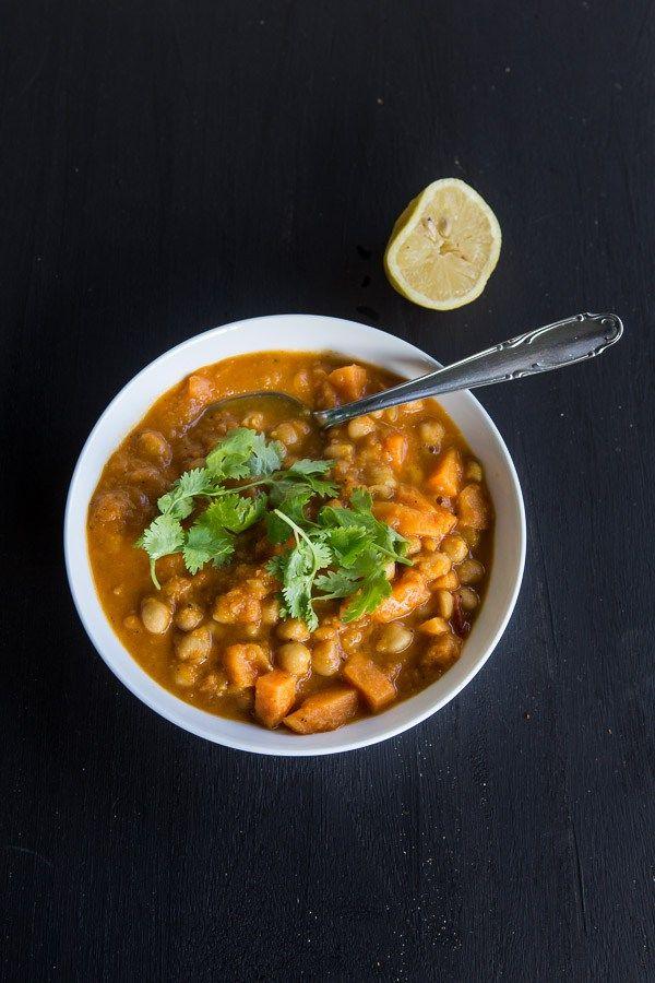Leckeres, veganes Curry mit Süßkartoffeln, Tomaten, Kichererbsen und Koriander, dazu ein wenig frisch gepresster Zitronensaft.