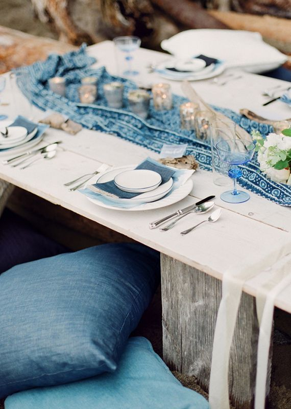 Create a cozy outdoor seating with soft pillows, rustic tables and relaxed table setting.