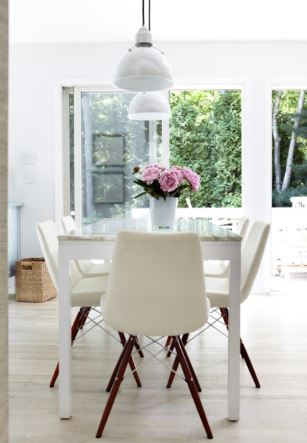 Perfect white dining room.  Simplicity at its best.  Light floors, nice modern chairs with Eames like base, white marble top table and pink roses overlooking a great garden view.  Like. http://cococozy.com