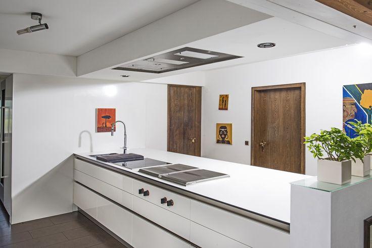 Blick auf die Kochinsel der Next125 Küchen mit den eingebauten Gaggenau Kochstellen und der in die abgehängte Decke intergrierten Gutmann Deckenlüftung Campo.Daniel Psotta von schwabenkuechen.de plante und realisierte diese Küche.