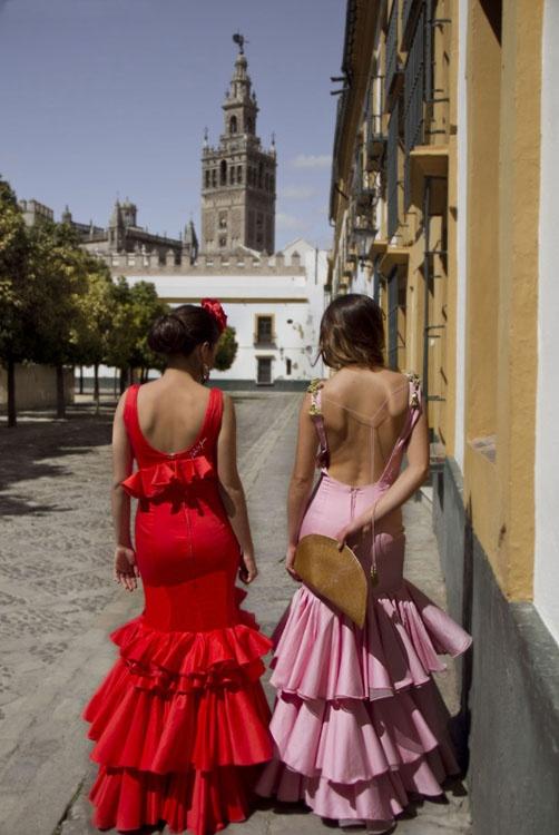 Traje de flamenca Clavel color coral, con volante que rodea el cuerpo. Contaba la leyenda que la convirtió en clavel para llevarla en su solapa. Traje de flamenca Buganvilla en rosa con hombreras de nudos marineros y borlas doradas.