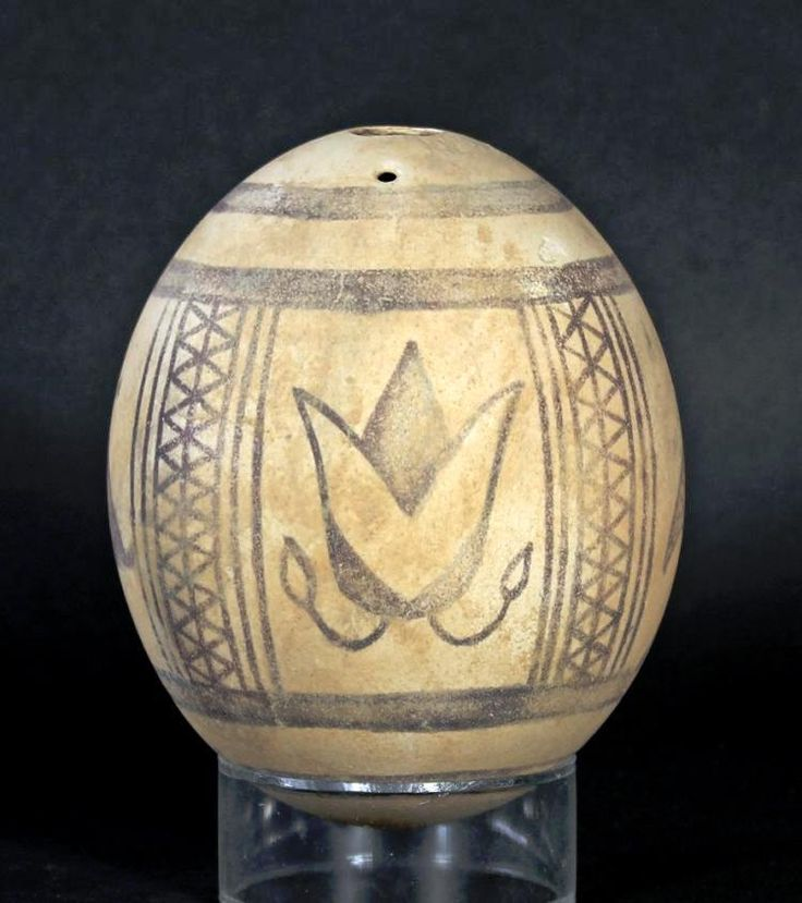 Phoenician Painted Ostrich Egg - 8th-6th Century BCAn ancient ostrich egg painted with four Panels divided by cross hatched bands. The scenes include, two lotus buds, a small tree, and an abstract symbol of the goddess Tanit.The use of the ostrich egg as a vase or decorative object dates back to the earliest Egyptian and Mesopotamian cultures. The painted ostrich egg was, however, especially popular among the Phoenician (Punic) people. Examples have been found in tombs at Carthage and at…