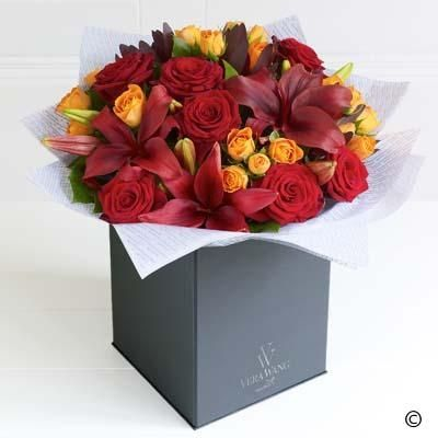 A celebration of the warmest, most vibrant natural colours, this magnificent Vera Wang bouquet is a striking statement piece. The scarlet, large-headed roses pair with the crimson red Asiatic lilies perfectly. Adding rich burgundy leucadendron and orange spray roses creates a vibrant mix of colour and a very opulent gift.