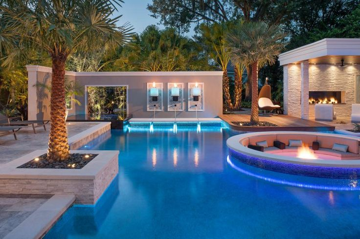 This tropical pool features a sunken seating area with fire pit and is surrounded by attractive stone pavers. An ipe wood walkway and an in-wall fire feature add to the luxurious feel of the space.