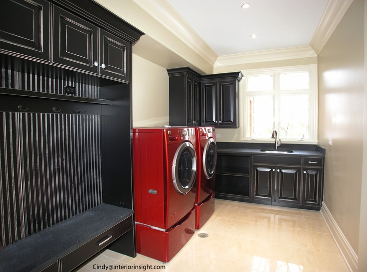 Mudroom with RED wash machines and black wainscotting builtin coat rack and bench. Black cabinets crystal ball door pulls and counter ceiling crown moulding