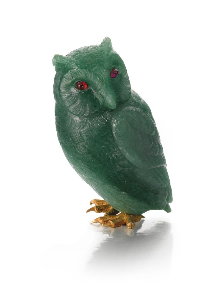 A HARDSTONE OWL, PROBABLY FABERGÉ, CIRCA 1910 carved of green agate, the eyes set with cabochon rubies, gold feet, apparently unmarked height 5.5cm, 2 1/8 in.