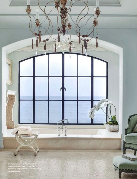 Beautiful Bedrooms and Baths | Large arched airy window and large airy chandelier in a California home.