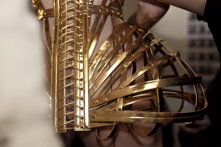 Collection Haute Couture automne-hiver 2012-13    Modèle n°57  Dévoreuse : Corset cage à basques, baleiné et lacé de cuir or, hanches et seins projetées.     www.jeanpaulgaultier.com #JPGaultier #PFW #couture #corset #cage